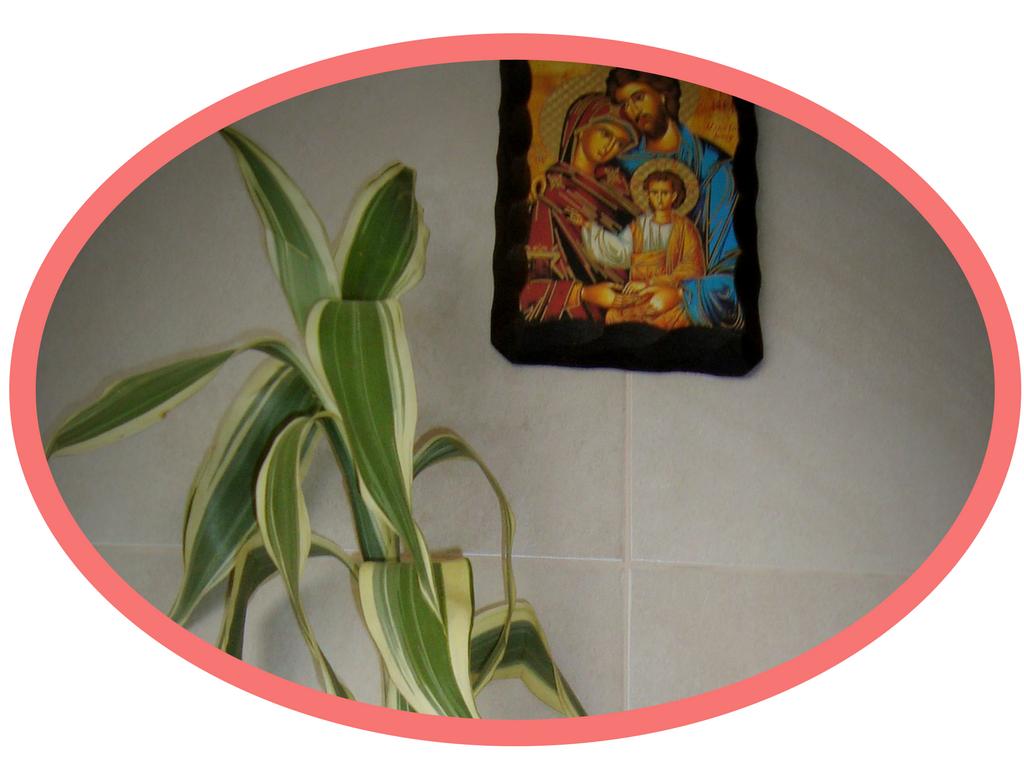 Wielkanoc wEkwadorze. Napierwszym planie palma, czyli gałązka bambusowa zzielono-żółtymi liśćmi. Nadrugim planie obrazem Świętej Rodziny.